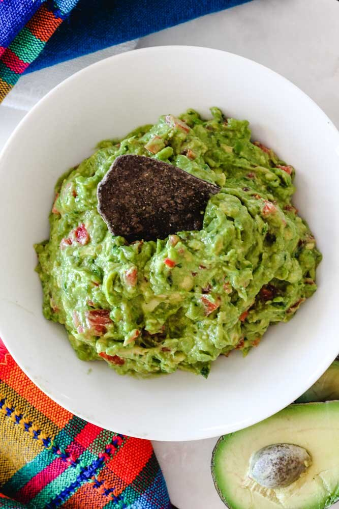 An overhead shot of guacamole with a chip in the middle. Post includes guacamole recipe - easy!